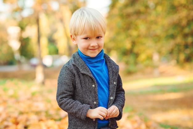 Милый белокурый мальчик малыша гуляет в осеннем парке. детская мода. маленький мальчик в теплой куртке.