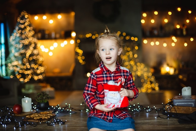 Cute blonde toddler girl in a checkered red shirt gets a christmas gift .