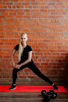 Cute blonde woman doing fitness on the background of a brick wall of the house during quarantine.