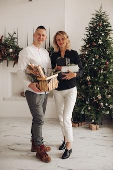 Милая блондинка держит подарочные коробки, стоя рядом со своим партнером и глядя прямо в камеру