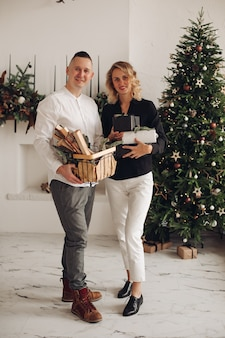 Cute blonde woman holding gift boxes while standing near her partner and looking straight at camera