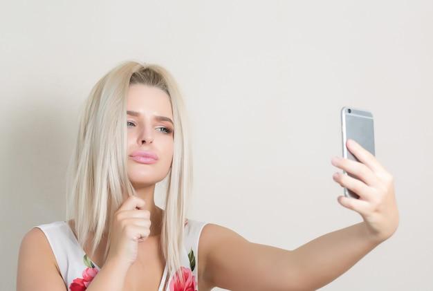 灰色の背景に対してスマートフォンで自画像を作るかわいい金髪の女性