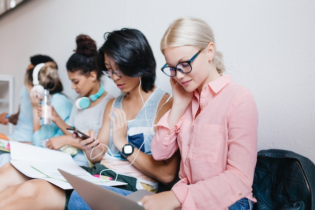 Cute blonde woman in pink blouse holding laptop and listening music in earphones with brunette male friend in glasses. indoor portrait of stylish international students relaxing in headphones.