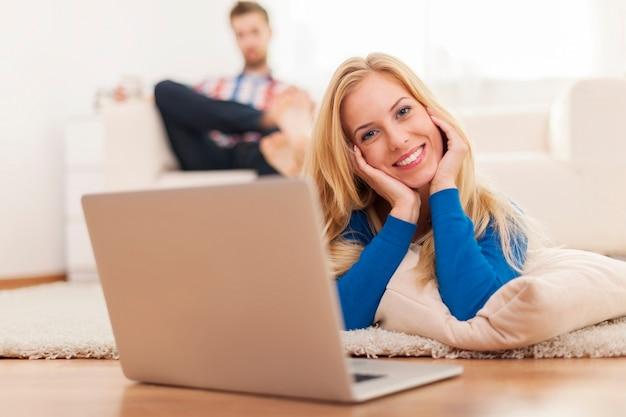 Donna bionda sveglia che si distende con il computer portatile sul tappeto a casa