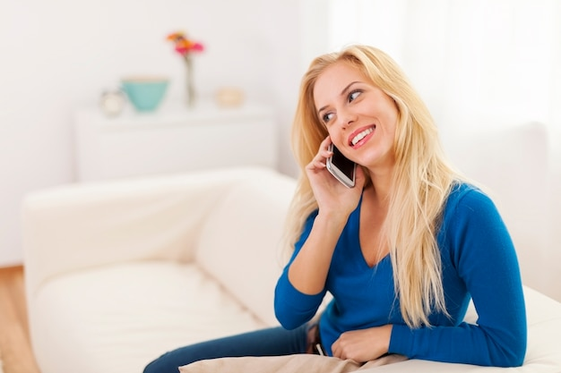 自宅で携帯電話で話しているかわいい金髪の女性