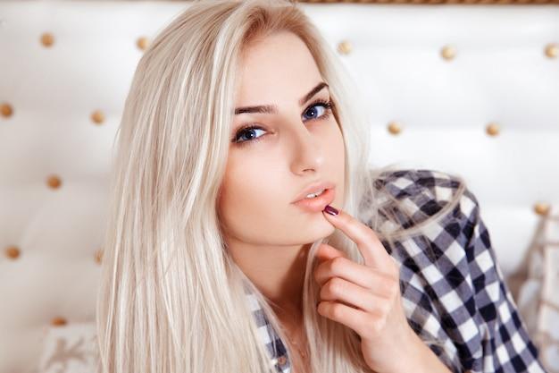 屋内でカメラを見ている青い目を持つかわいい金髪の女性