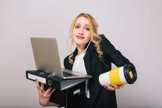 Милая белокурая молодая женщина офиса в белой рубашке, черной куртке, с ноутбуком, папкой, кофе, чтобы пойти изолированными. выражение настоящих эмоций, успех, работа, веселье