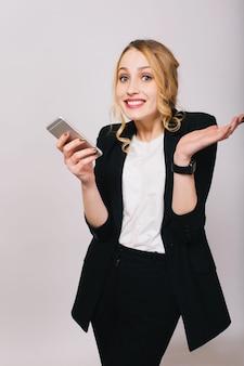 흰 셔츠에 귀여운 금발의 젊은 사무실 여자, 고립 된 찾고 전화와 검은 양복. 진정한 긍정적 인 감정, 성공, 일, 친절한 표현