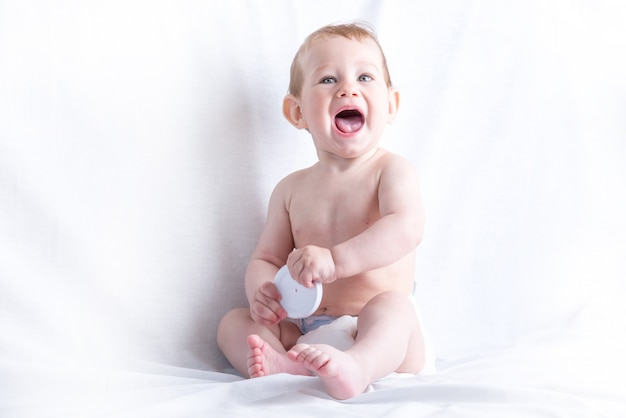 Cute blue-eyed baby 6-9 months smiling and playing on white. children's emotions