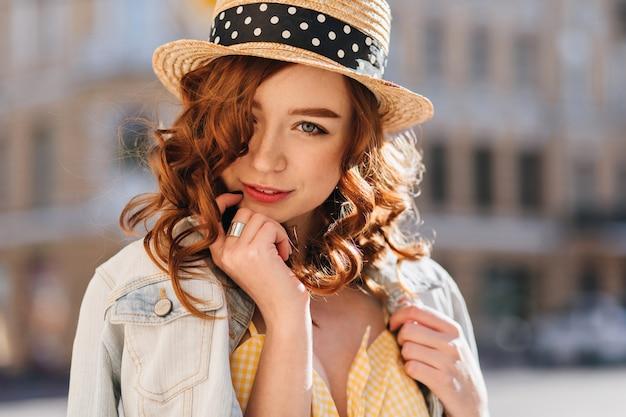 Ragazza sveglia dello zenzero dagli occhi azzurri in posa sulla città di sfocatura. foto all'aperto di una splendida giovane donna dai capelli rossi in giacca alla moda.