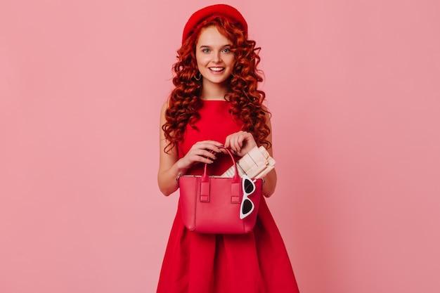 フレンチベレー帽と真っ赤なドレスを着たかわいい青い目の女の子が革のバッグでポーズをとり、新聞とサングラスが入っています。