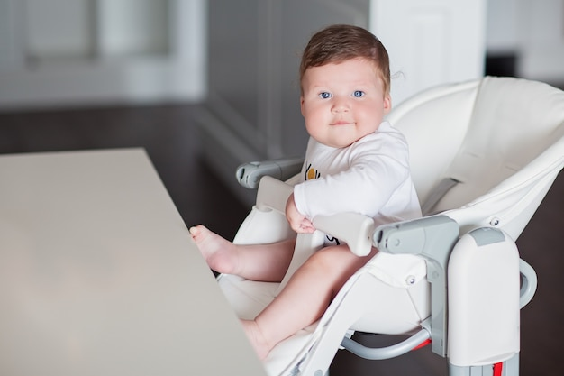 白い高い椅子に座っているかわいい青い目の小さな男の子。高品質の写真