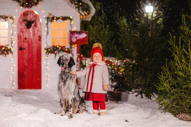 Симпатичная голубоглазая девочка в красной шапочке и пальто, лаская серую собаку в снегу