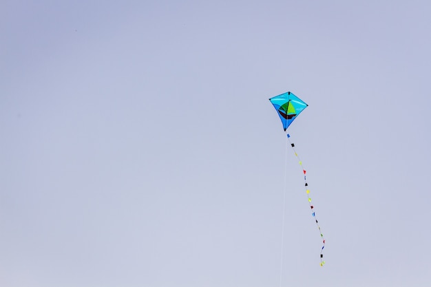 Cute blue kite flying on blue sky