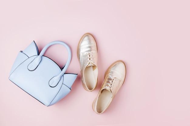 かわいい青いレディースバッグとスタイリッシュな金色の靴。フラットレイ、上面図。パステルカラーの春のファッションコンセプト