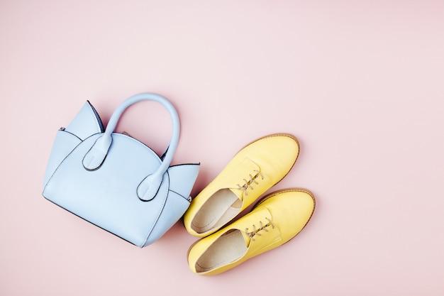 かわいい青いレディースバッグとスタイリッシュな黄色の靴。フラットレイ、上面図。パステルカラーの春のファッションコンセプト