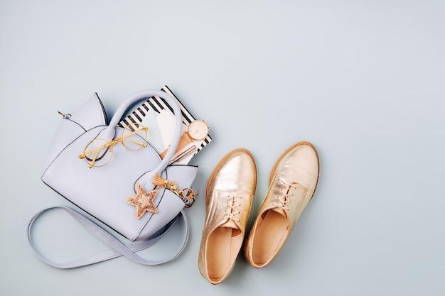 かわいいブルーのレディースバッグ、スタイリッシュなゴールデンシューズ、フェミニンなアクセサリー。フラットレイ、上面図。パステルカラーの春のファッションコンセプト