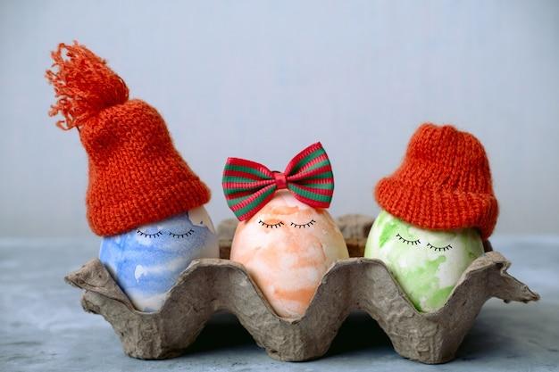 面白いニット帽子と弓でかわいい青、オレンジ、緑のイースターエッグ