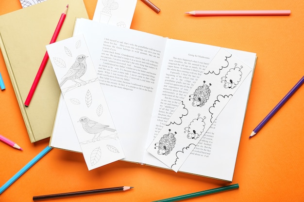 Cute bookmarks with books and pencils on color table