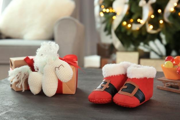クリスマスの装飾された部屋のテーブルの上の赤ちゃんとおもちゃのためのかわいいブーツ