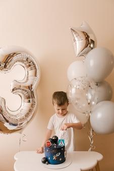 3歳のかわいい男の子が彼の誕生日を祝って、おいしい美しいケーキを食べています、風船を持った子供の写真