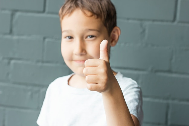Cute boy 8 years old showing thumbs up on background of grey brick wall