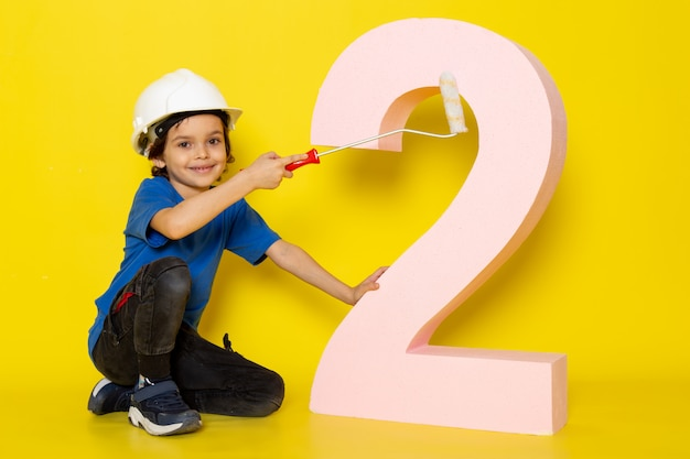 Cute boy adorable sweet in blue t-shirt and dark trousers near number figure on yellow wall