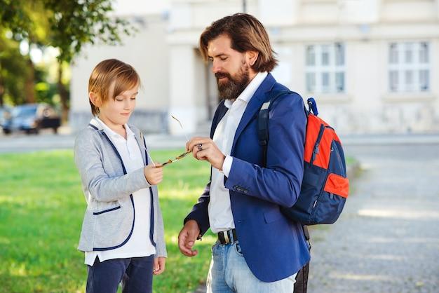 かわいい男の子と父親が学校に歩いています。屋外でファッションスーツを着ている息子とひげを生やした男