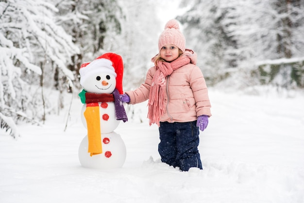 하얀 겨울 숲에서 귀여운 소년과 소녀 건물 눈사람