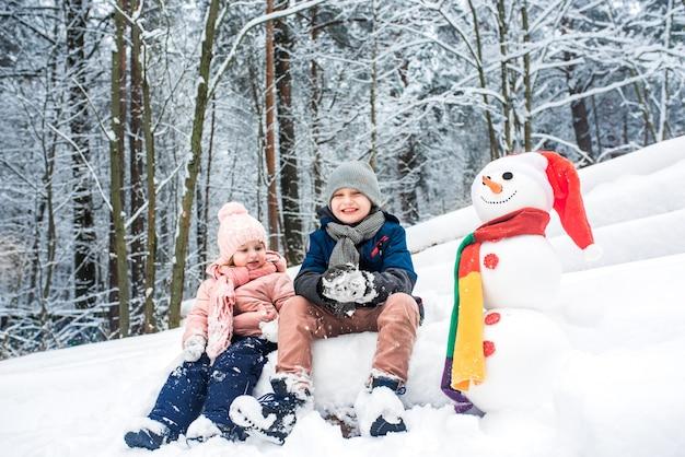 귀여운 소년과 소녀 겨울 하얀 숲에서 눈사람을 구축
