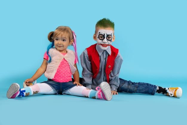 Милый мальчик и девочка на хэллоуин. дети сидят на шпагате и радостно улыбаются. фото хеллоуина на голубой стене.