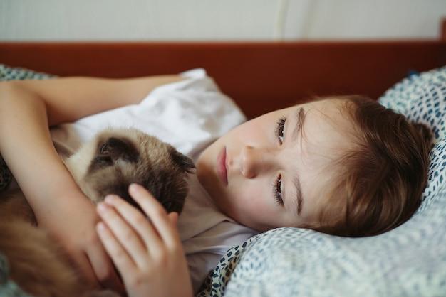 귀여운 소년과 그의 고양이는 아침에 침대에서 껴안고. 집에서 아이와 그의 고양이. 어린이와 애완 동물. 그의 동물과 함께 사랑스러운 아이. 아침에 아늑한 집. 국내 고양이와 아이의 우정.