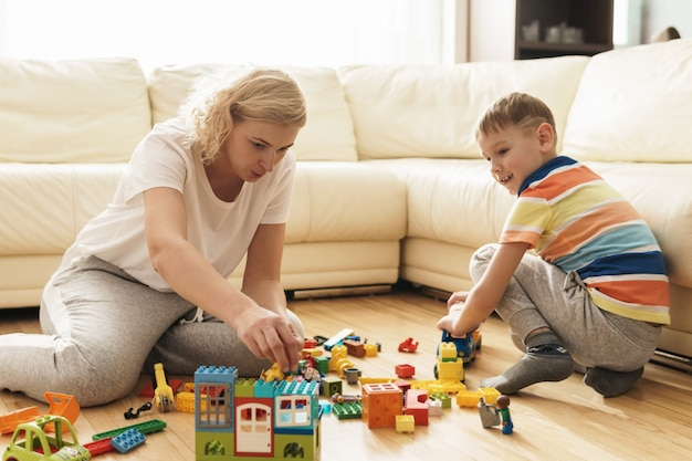 Милый мальчик и его счастливая мать играют вместе дома