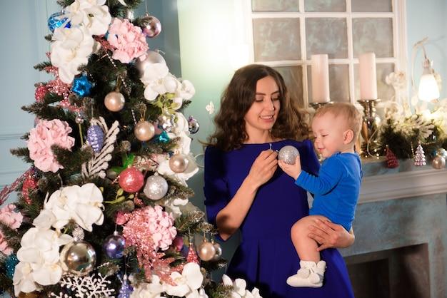 休日のクリスマスツリーを飾るかわいい男の子と彼の母親