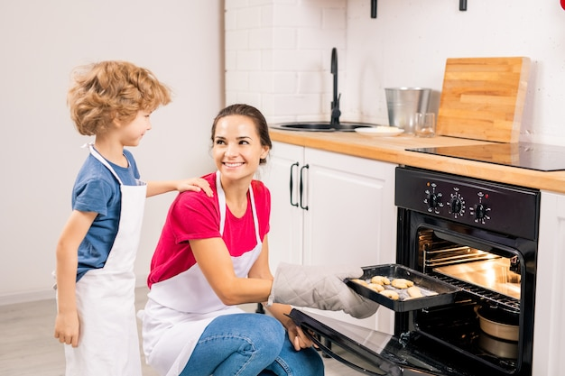 Cute boy in apron talking to his mom putting tray with raw cookies into oven while cooking together in the kitchen
