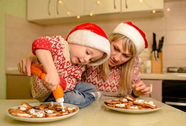 Cute boy bake homemade festive gingerbreads. funny child prepare holiday food for santa clause. santa kid making cookie for family in cozy kitchen. santa helper.