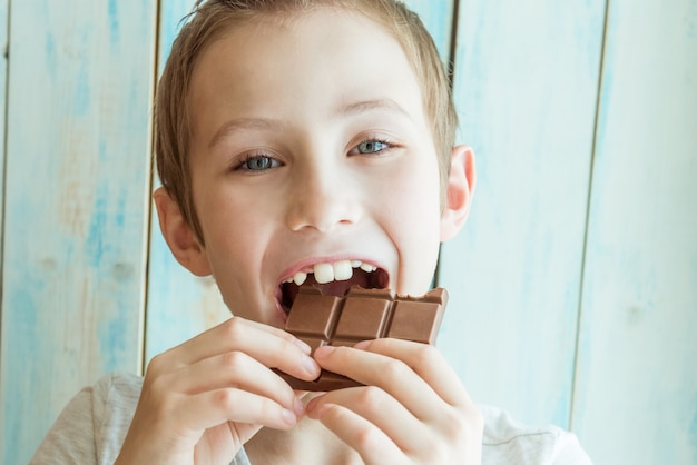 Cute boy bites off a brown chocolate bar. the concept of damage to your teeth from sweets