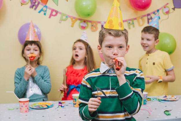 Cute boy blowing noisemaker on birthday party