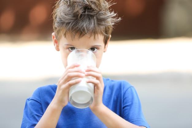 Cute boy in blue shirt drinking milk on blurred