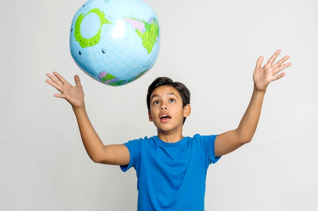 Cute boy in casual playing with a planet earth in studio