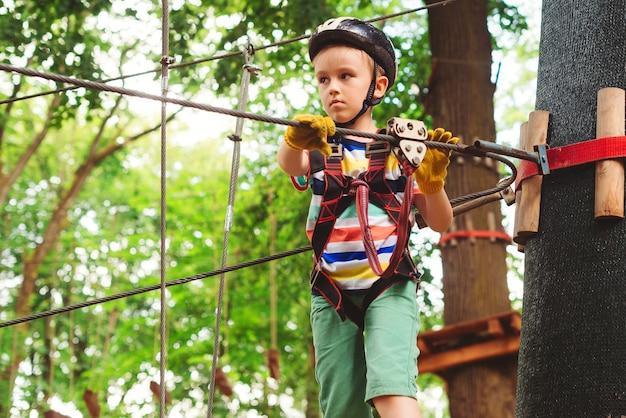 모험 공원에서 높은 로프 코스를 등반하는 귀여운 소년. 안전 헬멧에 아이, 익스트림 스포츠. 아이들을위한 여름 캠프. 나무 사이 높은 케이블 경로를 지나가는 아이.
