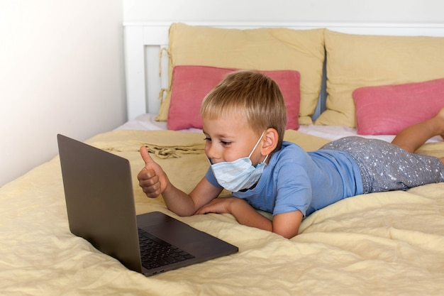Симпатичный мальчик общается по видеосвязи, используя ноутбук в медицинской маске