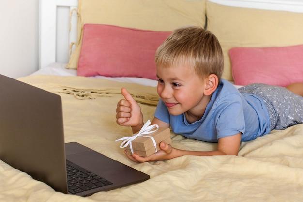 Милый мальчик поздравляет по видеосвязи и дарит подарок