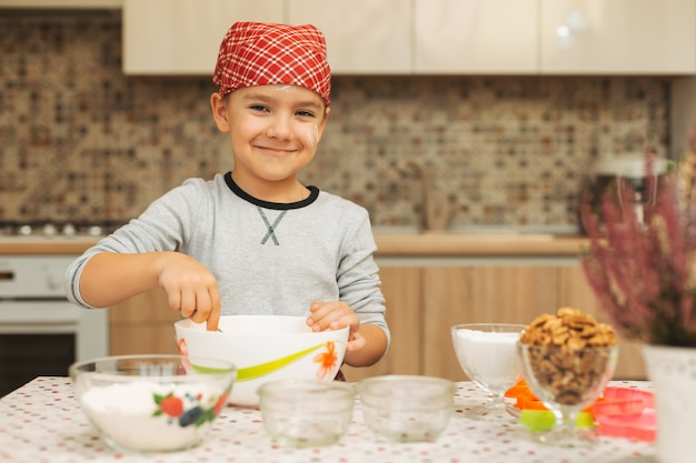 かわいい男の子がカメラを探して自宅の台所で料理