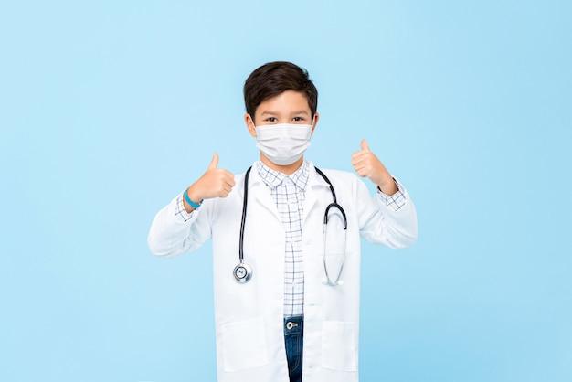 의료 마스크를 착용하고 엄지 손가락을주는 귀여운 소년 의사는 밝은 파란색에 고립
