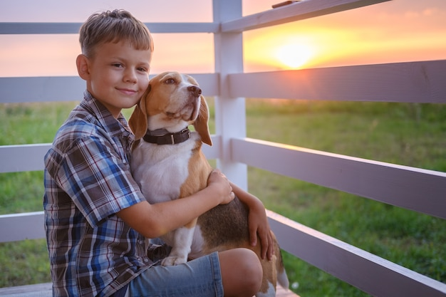 Cute boy and dog beagle sitting hugging on the veranda of the house on a summer evening against the sunset