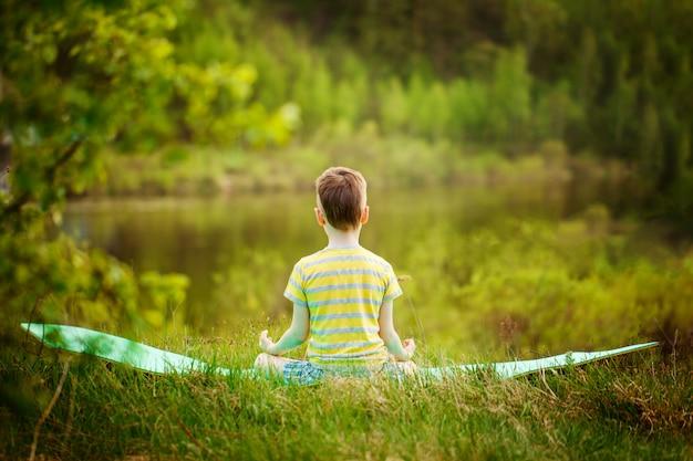 自然でヨガをしているかわいい男の子。夏の公園で演習を行うスポーティな小さな男の子。