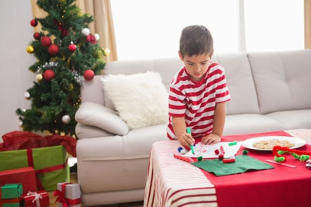 Симпатичный мальчик рисует праздничные фотографии