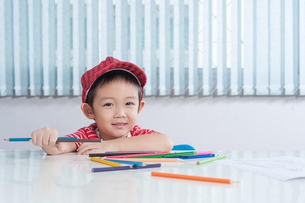 귀여운 소년은 어린이 방에서 컬러 연필로 그립니다.