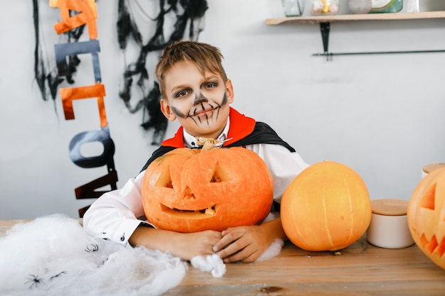 Cute boy dressed as dracula at a party on halloween holding a pumpkin on a background of scenery. high quality photo